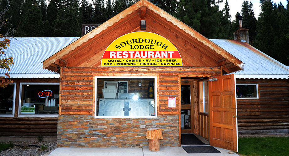 Text: Sourdough Lodge. Restaurant. Motel. Cabins. RV. Ice. Beer. Pop. Propane. Fishing. Supplies. Open.
